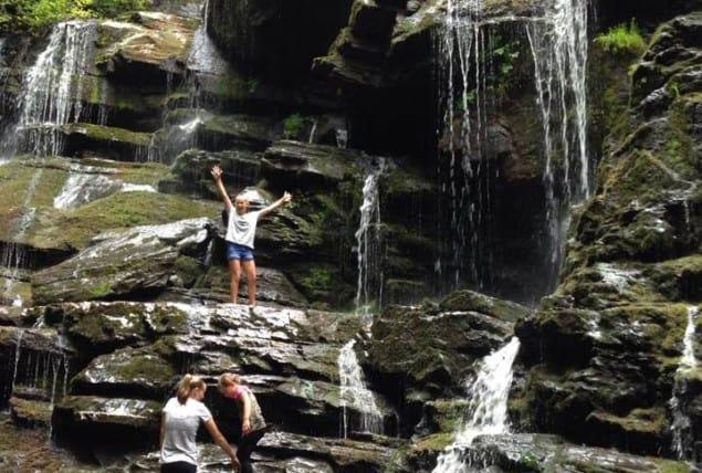 photo of kids under waterfall