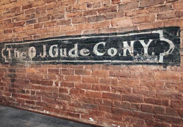 photo of The OJ Gude Co NY painted on brick wall