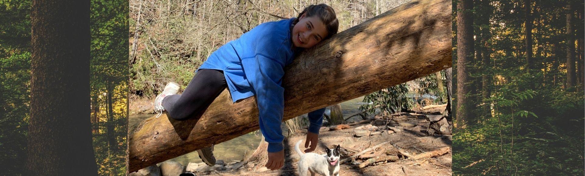 photo of girl on a log and dog