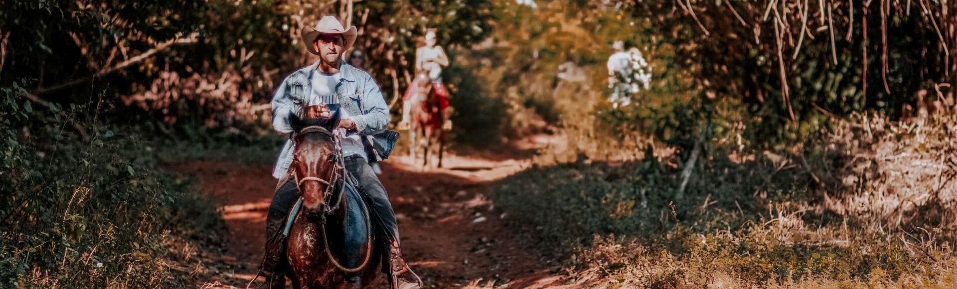 photo of man riding a horse